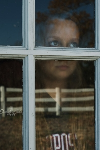 young lady looking out window